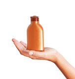 Hand holding plastic bottle for sun lotion isolated on white bac