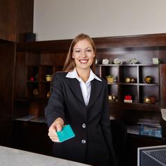 Empfangsdame im Hotel überreicht Schlüsselkarte