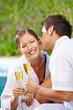 Mann küsst Frau mit Sekt am Pool