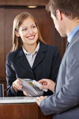 Gast bezahlt im Hotel mit Smartphone
