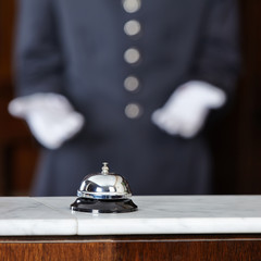 Concierge zeigt auf Tischglocke