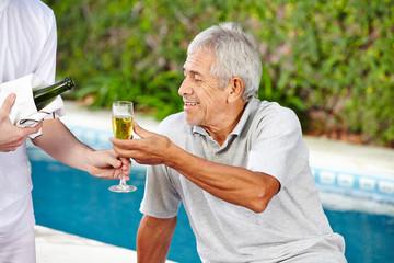 Senior bekommt Sekt vom Kellner