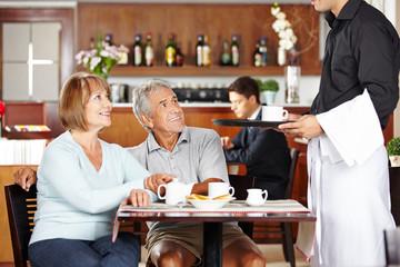 Kellner bedient Senioren im Café