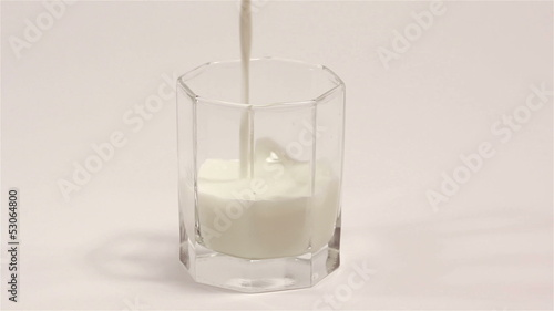 Milk flowing in  transparent cup on  white background