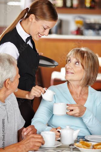 Kellnerin schenkt Seniorin Milch in den Kaffee