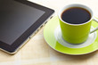 black coffee in green cup with computer tablet