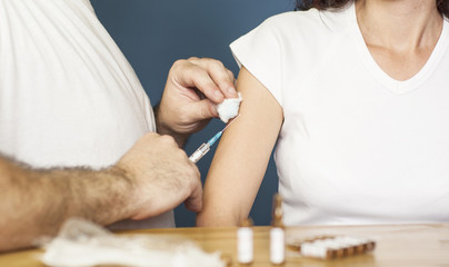 Doctor preparing to vaccinate a woman against flu