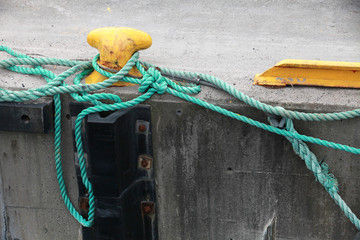 Yellow mooring bollard with green naval rope