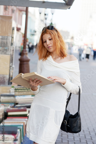 girl selects the book from street shop