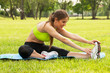 Beautiful young woman exercising on a grass