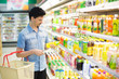 man in a supermarket buying a bottle of juice