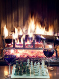 play chess drinking red wine in front of  roaring fireplace