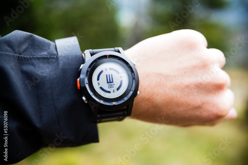 Hiker on mountain trail checking compass
