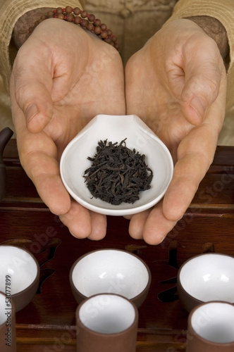 Tea in hands of tea ceremony master close up