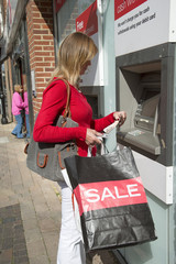 Female shopper using a cash dispenser