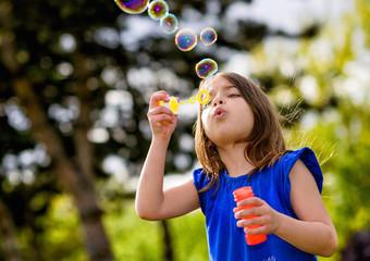 beautiful child blowing bubbles