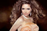 Beautiful woman with long brown curly hair and makeup. Hairstyle