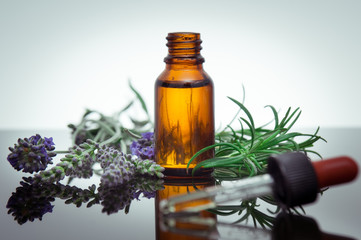 Essential oil bottle with lavender flowers and rosemary