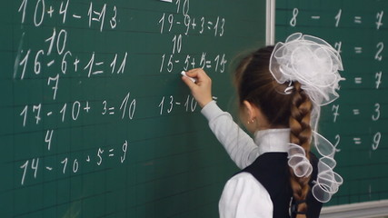 schoolgirl writing on blackboard in classroom