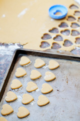 Heart shaped raw cookies on metal baking tray, selective focus