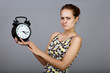 Angry girl with alarm clock at gray background