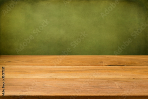 Empty wooden table over grunge green background