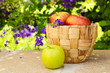 Basket with apples on stone surface over beautiful flower garden