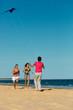 Man and women running on beach with kite