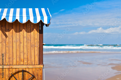 Wooden stall with awning over sea and sky background