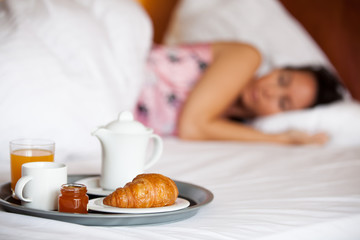 Frau schläft im Hotelbett und Frühstück steht bereit