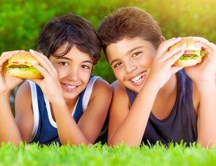 Two boys eating burgers