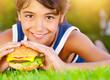 Pretty boy eat burger outdoors