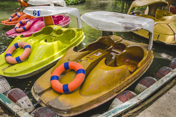 A row of bright paddle boats