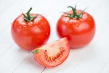 Ripe red tomatoes and their segment on wooden boards