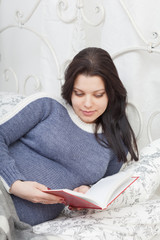 Pregnant woman reads the book, lying in a bed