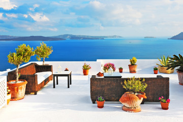 Outdoor tables and sofas on roof terrace overlooking sea in Oia