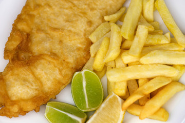 Salted french fries with large serving of fried fish with lemon