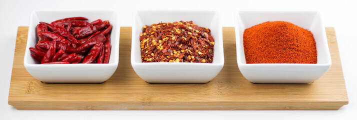 Whole chili peppers, flakes, and chili powder isolated on white
