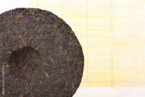 Disc of chinese puer tea on wooden background