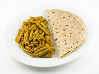 Indian roti and green bean sabzi on white background