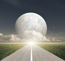 Road between meadow fields and Giant Moon with clouds at horizon
