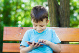 Young boy sitting on bench with tablet