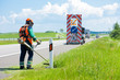 Leinwanddruck Bild - Road landscapers cutting grass around mileposts