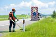 Leinwandbild Motiv Road landscapers cutting grass around mileposts