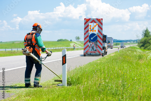 Road landscapers cutting grass around mileposts