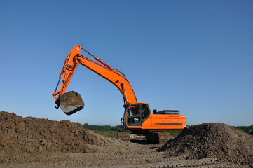 Excavator at work in open sand mine and a blue sky