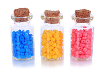 Different colorful beads in bottles isolated on white