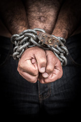 Hands of a shirtless  man chained with a  chain and a padlock