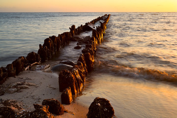 old breakwater in North sea at sunset