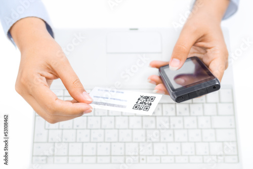 Hands holding smart phone and business card with qr code